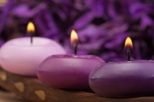 three burning purple toned candles with purple background